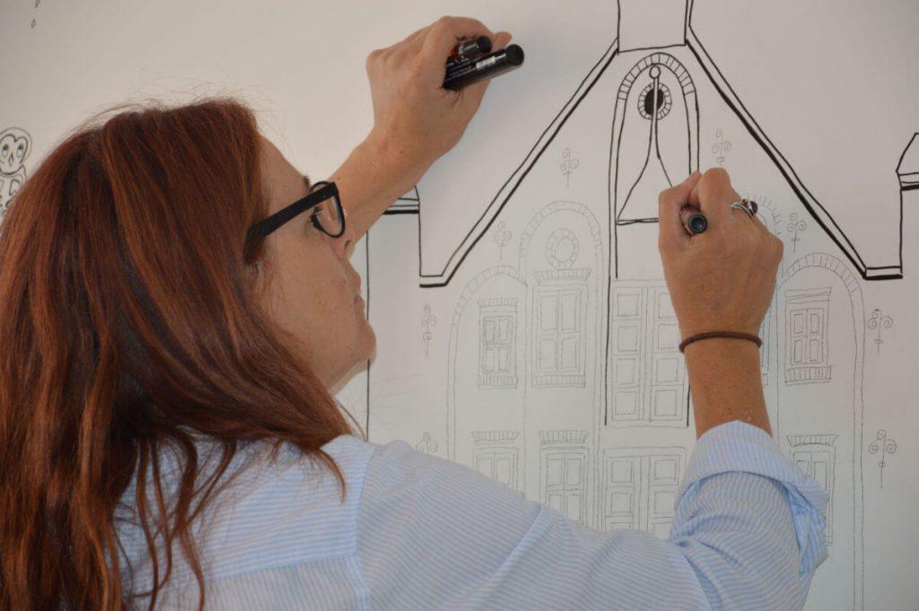 Illustrator maakt muurschildering